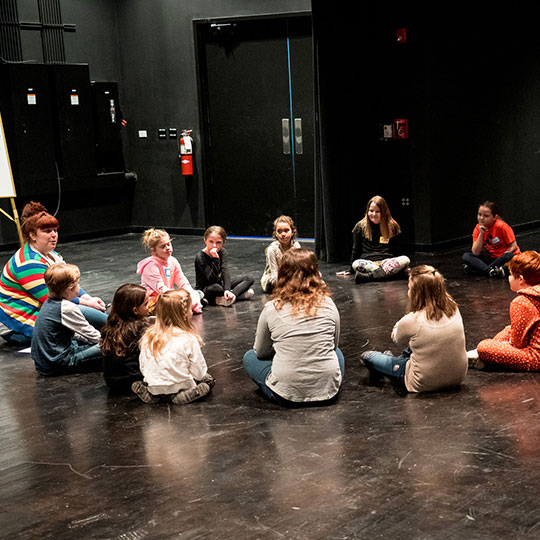 Children sit in a circle and learn in a creative drama class
