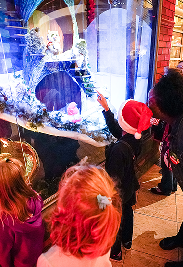 Young boy in a Santa hat pointing to a Merry Makeover display in the Kettering Wintergarden at the Schuster Center
