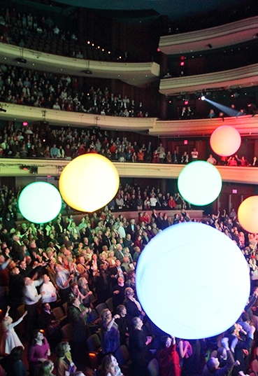 Audience celebrating with glowing light balls at the Schuster Center