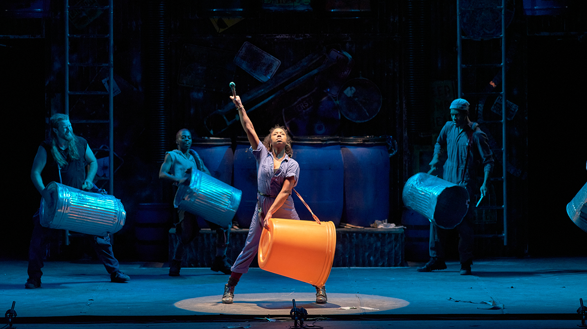 A dancer stands center stage as she uses a large plastic trashcan as a drum.