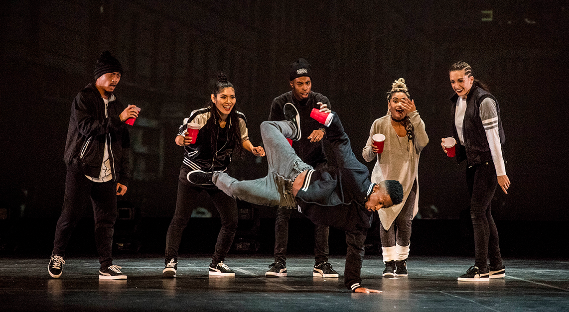 A group of dancers break dance on stage.