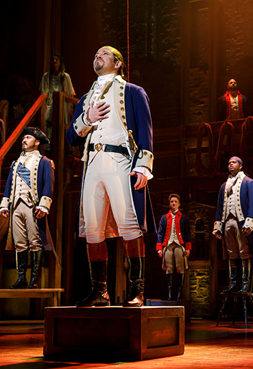 Actors stand on stage in revolutionary military uniforms.