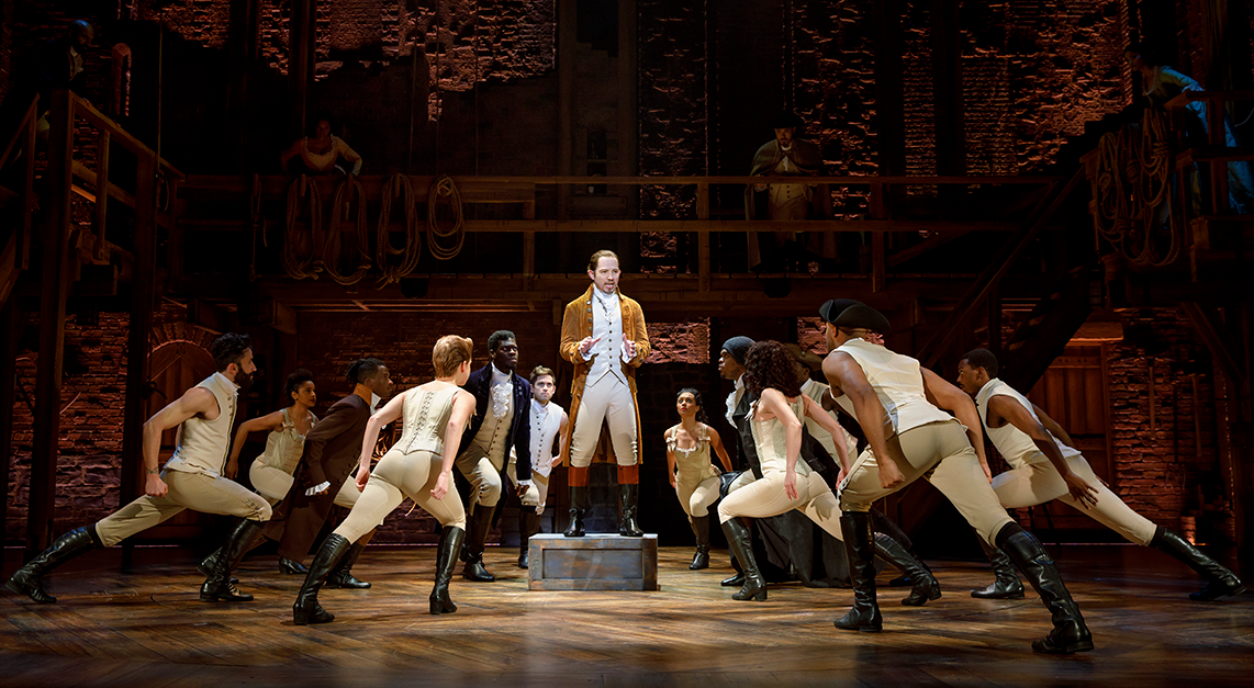 An actor stands center stage while dancers surround him.