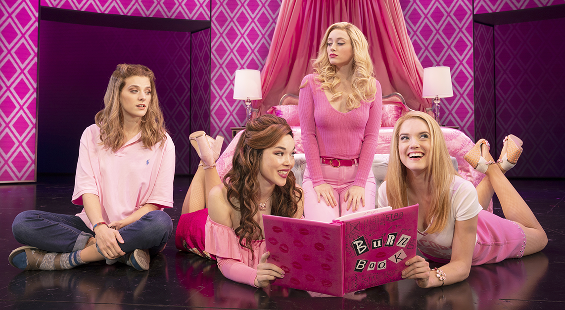 Three teenage girls wearing all pink read a book with mean things written in it while a fourth girl looks on.