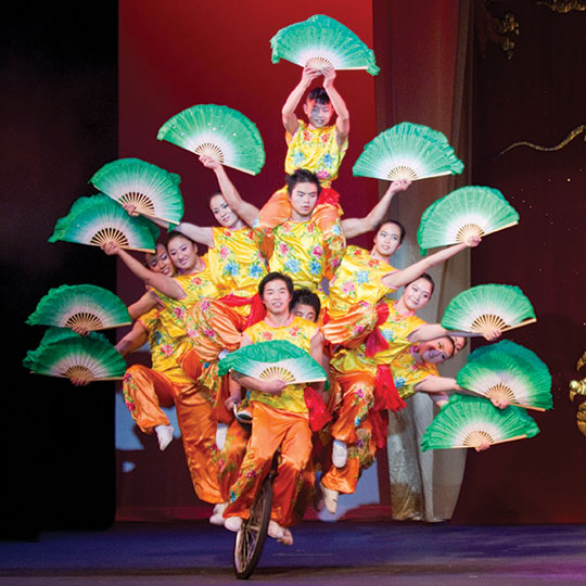 Group of acrobats on a unicycle holding Chinese fans.