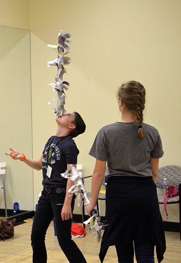 A boy balances a newspaper sculpture on his chin while a girl watches.