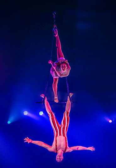 Two acrobats dangle from a trapeze