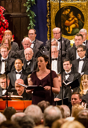 A woman sings in front of a choir dressed in tuxedos