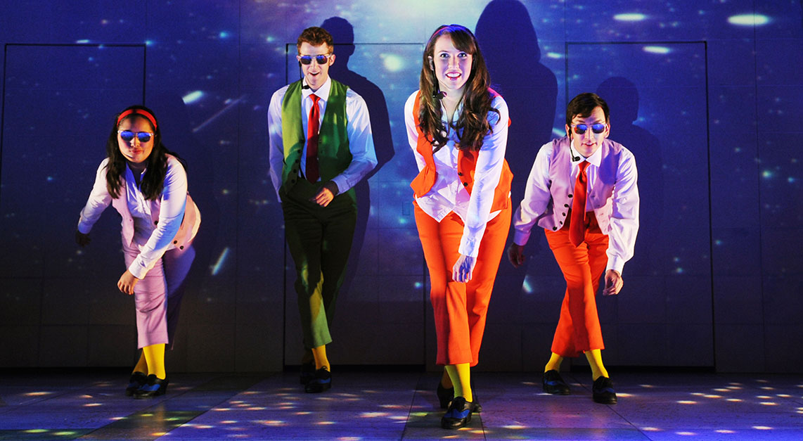 Actors dance on stage while wearing sunglasses