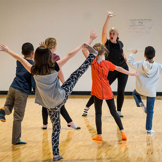 Children happily learn to dance from an instructor