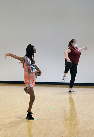 Students learn to dance from an instructor